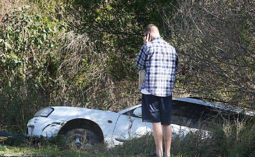 A sedan stuck down an embankment.