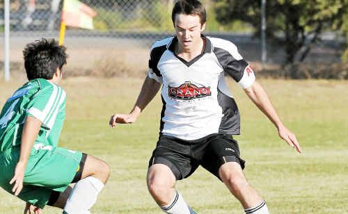 Central's Garth Lawrie takes on a Clinton player in the Cap League Soccer clash at Clinton Park on Sunday.