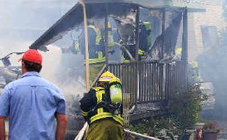 Fatal: Firefighters battle the fire which claimed an elderly woman's life at Chinderah.