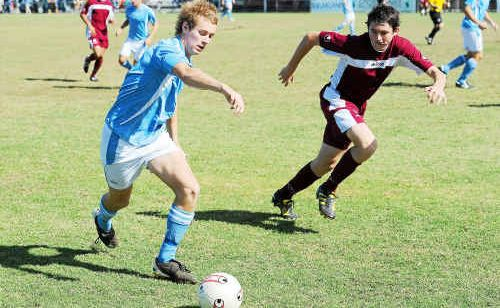 Bundaberg Spirit Youth player Jack Hambrecht make a run down the sideline with Scot Coulson from Queensland Academy of Sport Youth hot in pursuit.