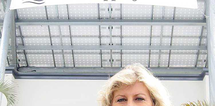 Ocean Village Shopping Centre manager Veronica O'Dwyer under the solar panel structure.