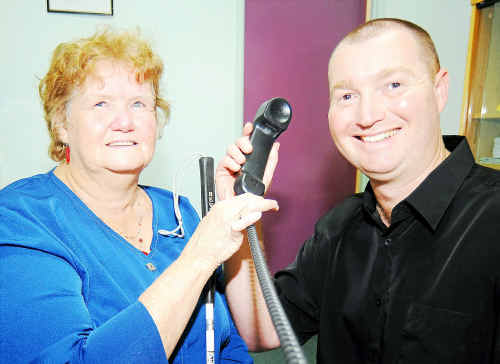 Vision impaired voter Patricia Stillman gets some assistance from divisional returning officer Trevor Jordan before she uses the telephone to cast her vote.