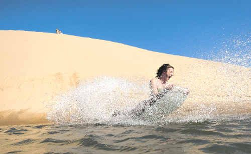 Sandboarding down 30m dunes and straight into the water on Middle Island is the latest adventure tourism blast.