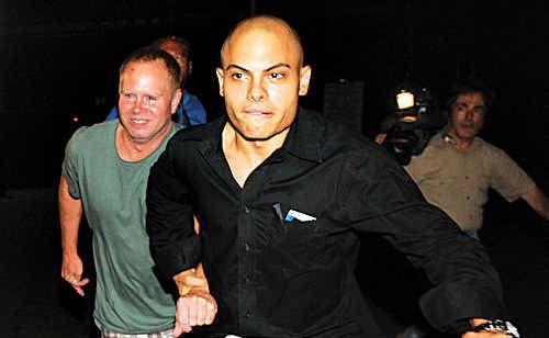Flight attendant Steven Slater, left, is led away after posting bail earlier this month.