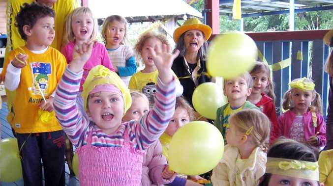 Mullumbimby Community Preschool kids get into the spirit of Daffodil Day with Col Davison and Di Davison.