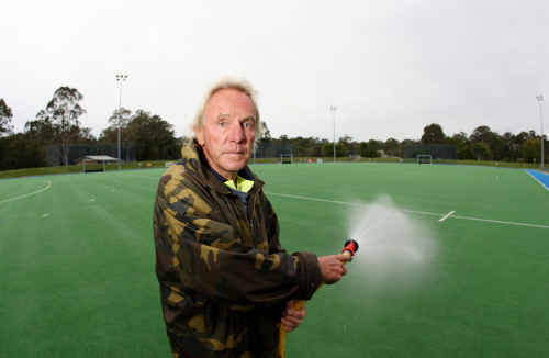 Sunshine Coast Hockey Association groundsman Peter Bannister waters the artificial turf. The club is one of many that will benefit from a council assistance package to subsidise water costs.