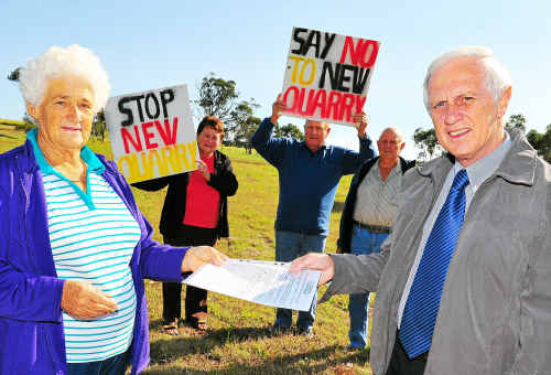 Vi Tapiolas with other Innes Park residents Adrianna Cocco, Gill Cocco and Jim Tapiolas, handing over an anti-quarry petition to Cr Danny Rowleson.