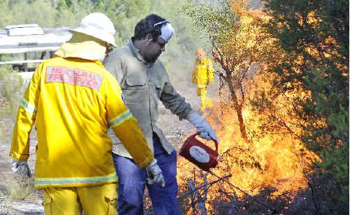 Wardell Rural Fire Service volunteer Karl Hearn instructs team member James Currie on lighting a fire for a back-burning operation at Wardell recently.