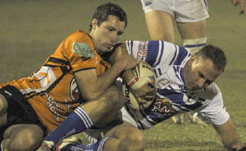 Jason Sykes tackles Nathan Cameron in the Brothers versus Wallabys Challenge Cup final at Marley Brown Oval, Gladstone.