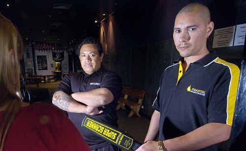 Rumaz nightclub owner Mark Vakauta looks on as head of security Jeff McDermott scans a patron.