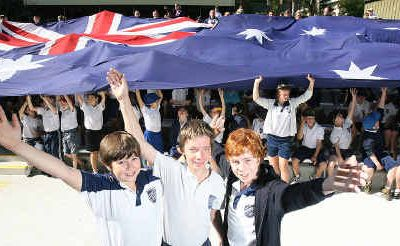 Nathaniel Williams, Aaron Ball and Jordan Zande with the Australian flag that flew over Parliament House in Canberra in 2001. Photo: Rob Williams SE0110WB