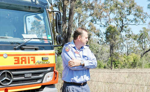 Queensland Fire and Rescue Service Warwick station officer Dennis Burton inspects bushland on the city border which surrounds Warwick houses.
