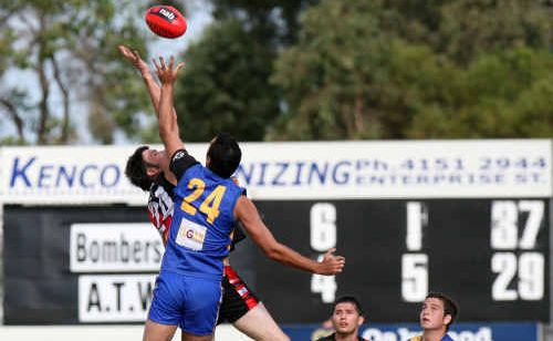 Rohan Mortimer of the Hervey Bay Bombers (left) and Steven Hill of Across the Waves compete for the ball during the semi-final in Bundaberg on Saturday.