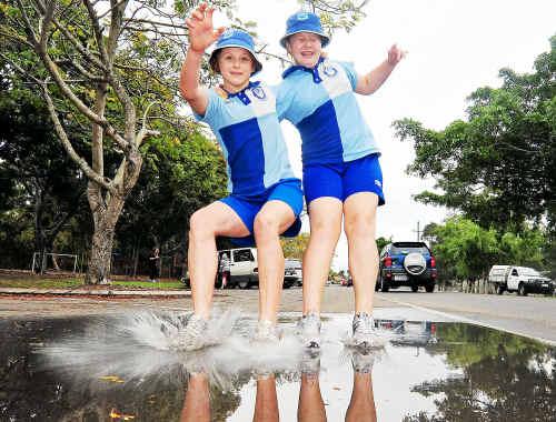 Bundaberg South State School students Aimee Bishop and Kiana Wondrock enjoy the wet weather.