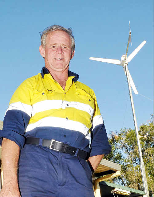 John Humphreys and his private wind turbine he installed to generate electricity.