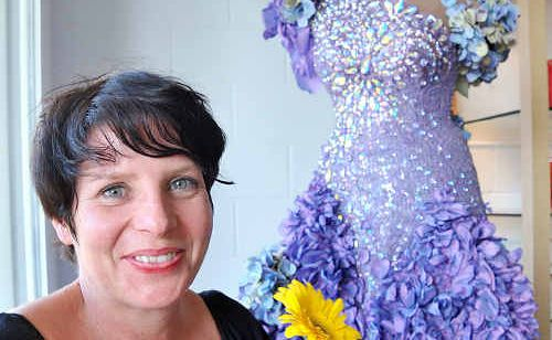 Amanda Court from Flax Flower with a dress worn by Delta Goodram which is on display in her Coolum floweer shop.