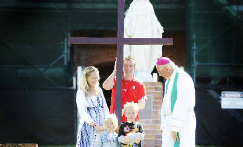 John O'Brien, assistant principal at St Carthage's Primary School in Lismore, holds the Mary MacKillop Cross at St Carthage's Cathedral in Lismore yesterday while the Bishop of Lismore, Geoffrey Jarrett, chats with his wife Michelle and their children Bella, 3, and Lochy, 6. Marc Stapelberg