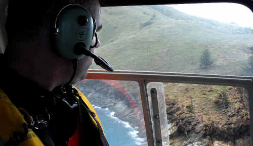 Mackay SES officer-in-charge Justin Englert in the RACQ-CQ Rescue helicopter searches St Bees Island.