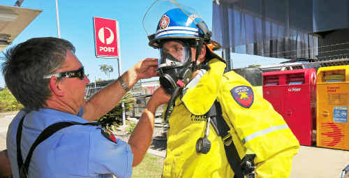 Senior Maryborough firefighter Graham Wex helps Brisbane-based Queensland Fire and Rescue scientific inspector Ray Bott suit up before going in the sorting area of the Australia Post delivery centre, where suspicious powder was found.