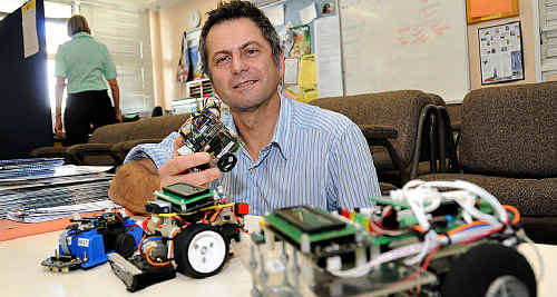 Gympie High science teacher Tony Grudzinski shows some of the robots his STEM students made.