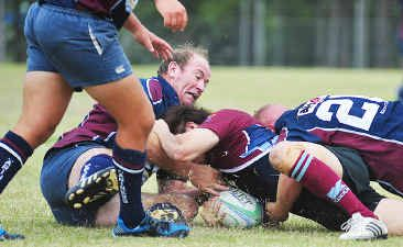 Veteran Andrew Beattie (left) helps tackle a University player while playing for the Fraser Coast Mariners in Hervey Bay on the weekend.