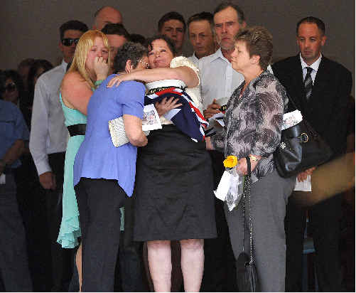 The family of AB Jay Wilkie embrace as mum Karen Bailey clutches the flag and sailor's cap presented to her at his funeral, held at the Bundaberg Bible Chapel.