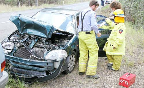 Queensland Fire and Rescue Service staff take details from the driver of a Honda Civic, one of five vehicles involved in a traffic accident at Apple Tree Creek yesterday.