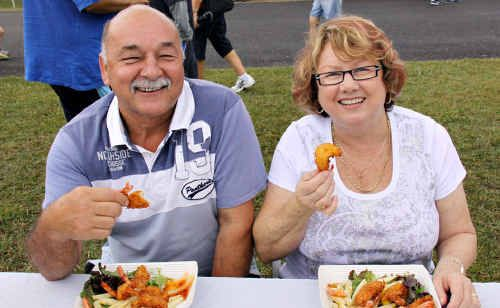 Troy Hudson took out the mullet throwing contest at Saturday's Tin Can Bay Seafood Festival where John and Julie Gorske, of the Gold Coast,  tucked into some freshly-cooked Bay produce.