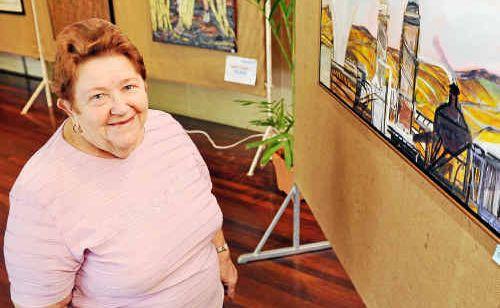Bundaberg Arts Festival Association secretary Merle Beran alongside the award-winning painting by Jennifer McDuff, titled Childers.