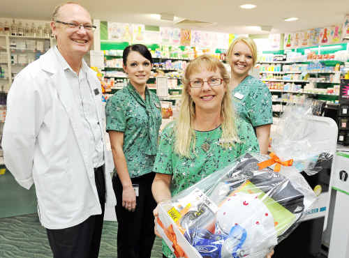Malouf Pharmacy staff members Brendan West, Rolinia Tremayne, Shari Mortensen and Cathie Wilk holding the raffle basket to raise money and awareness for the Walk to Cure Juvenile Diabetes.