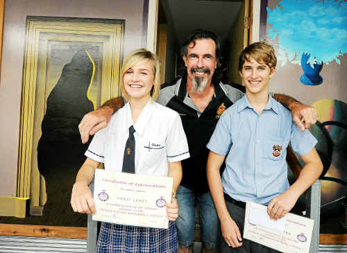Viet Nam veteran Wayne Gaynor presenting Shalom year ten students Annie Landt and Lachlan King with certificates in appreciation of the wonderful mural shalom student painted for the Viet Nam drop in centre.
