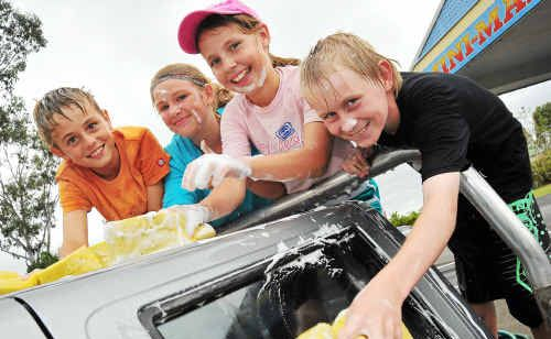 Dylan Cross, Taylor Collins, Montanah Rejtano and Colton Kleinitz from Moore Park State School washing cars to help raise money to get six students to the OptiMinds finals in Brisbane.