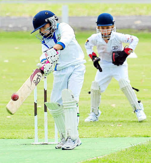 Brothers under 10's batsman Declan Buckley puts bat to ball as Norths wicketkeeper Zac Laybutt waits for a loose ball.
