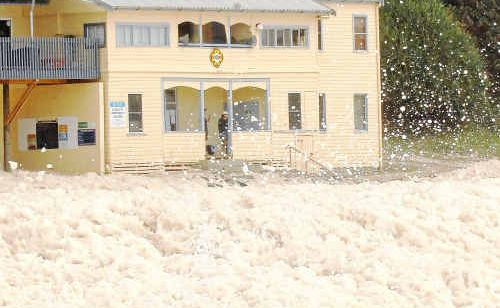 Foam more than a metre deep covered Main Beach at Yamba up to the steps of the surf club.