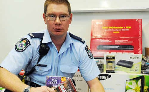 Constable Luke Norris with an estimated $3500 worth of stolen goods detectives found in a raid on a Gin Gin home.
