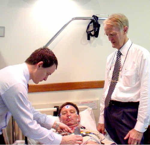 Sleep studies technician Damian Burnham, left, and sleep studies specialist Dr John Corbett attend to patient Gordon Ferguson.