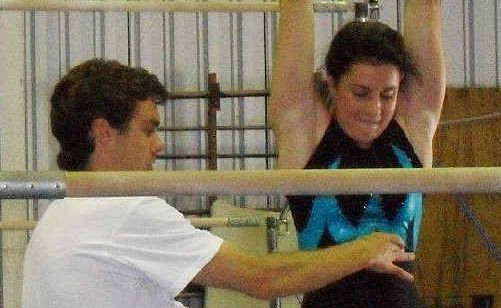 Coach Nathan Kingston instructs Clare Black on bars.