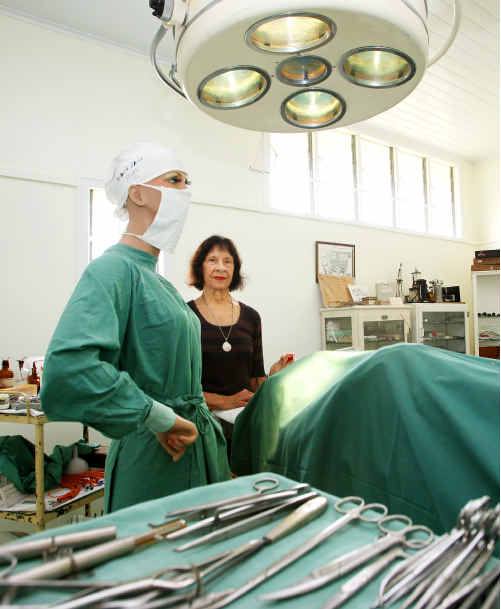 CUTTING CREW: Norma West joins a nurse scrubbed up to assist a surgeon in the museum's operating theatre.