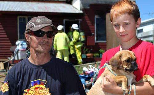 Jason and Harley Holohan with their dog Bella in front of their burnt-out house in Mt Morgan yesterday.