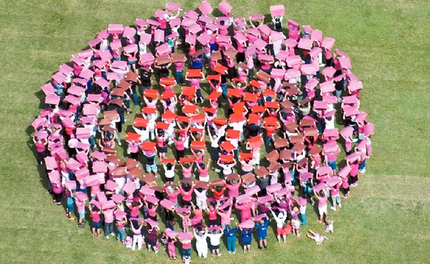 Hundreds of placard-carrying community member stand in formation at the showgrounds to create Mackay's Big Boob as part of a Cancer Council Queensland initiative aimed to raise awareness of breast cancer.