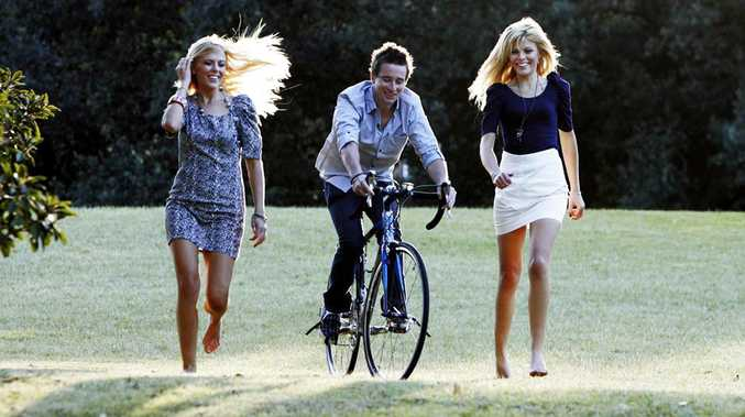 Lachlan Fyfe on his bike with two of his support team, twin sisters (L) Melanie and Zoie Swindells.