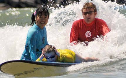 Gift of surfing: First-time surfer Olivia Sykes is helped onto a wave by big-hearted volunteers.