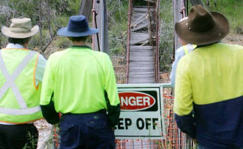 Council staff look over the footbridge at Mt Morgan soon after it collapsed.