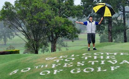 Rain check: As competitors in the 60th Festival of Golf duck for cover yesterday, Gurk Singh watches the heavens open.
