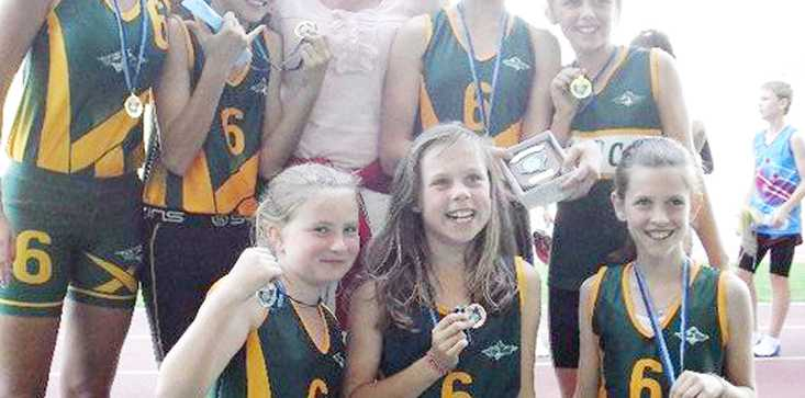 Members of the two medal-winning Byron Bay relay teams with coach Heather Farquhar.