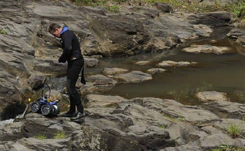 Tragic: A police diver prepares to enter the water at Hanging Rock Falls near Wadeville, north of Kyogle, in search of a missing 14-year-old boy. The teenager's body was recovered about 11am yesterday.