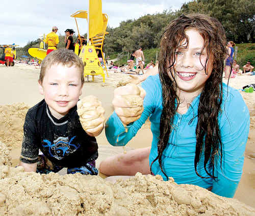 Narayan and Sivani Ball were able to build their sandcastles outside the flagged area at Mooloolaba Beach.
