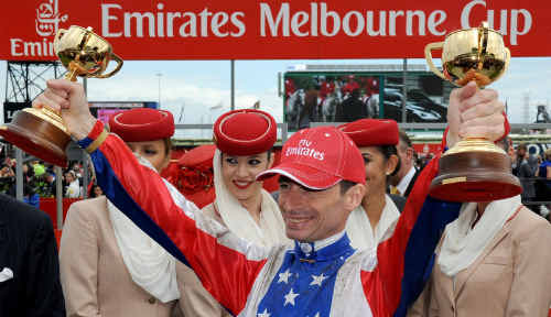 French jockey Gerald Mosse poses with trophies after winning the $6.1 million Melbourne Cup on Americain.