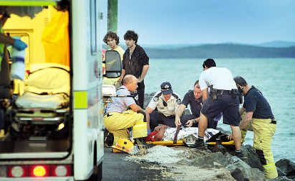 Emergency services attend to the injured driver of a 4WD that ran off the rock wall and into the ocean.
