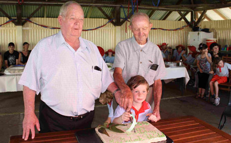 Past students Don Neumann and Vernon Andrews help Ma Ma Creek's youngest current student, Alex Evans, to cut the 130th birthday cake at Ma Ma Creek State School.